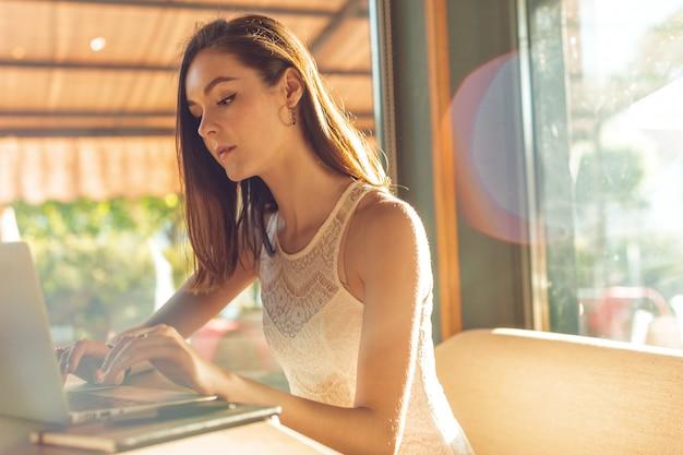 Mujer atractiva hermosa en el café con una computadora portátil que tiene un descanso para tomar café