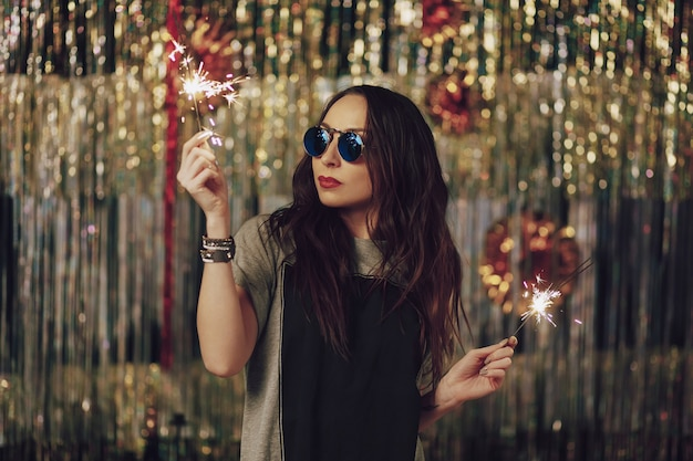 Mujer atractiva hipster con bengalas en las manos
