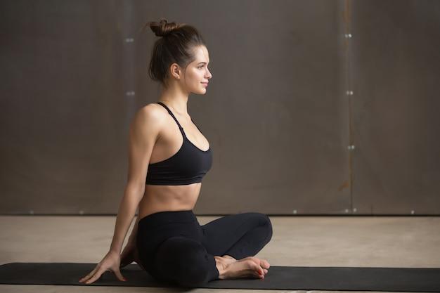 Mujer atractiva joven en la actitud de baddha konasana, parte posterior gris del estudio