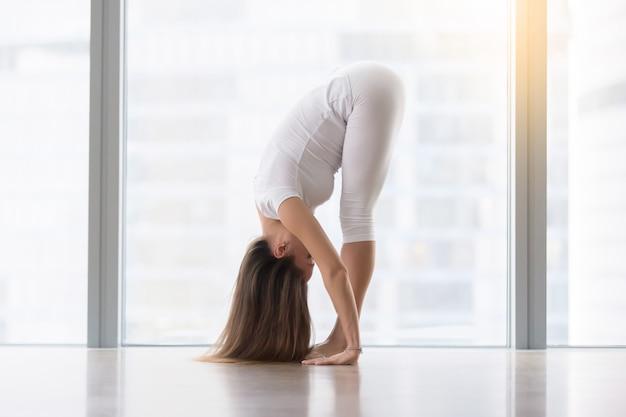 Mujer atractiva joven en actitud del uttanasana contra ventana del piso
