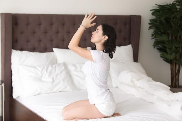 Mujer atractiva joven en actitud vajrasana en la cama del hotel