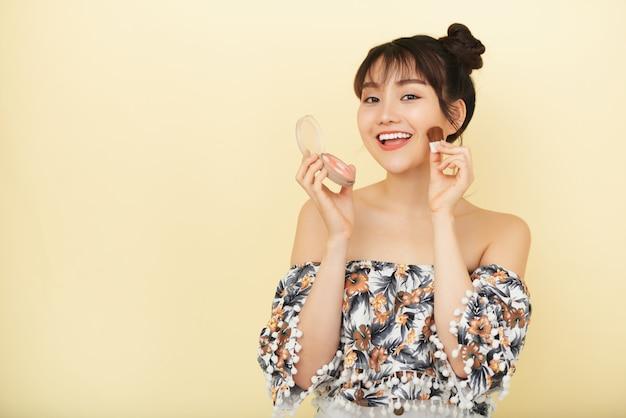 Mujer atractiva joven aplicando rubor en sus mejillas juguetonamente