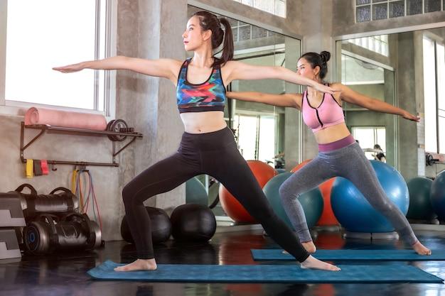 Mujer atractiva joven de asia y amigo que se extiende en el gimnasio.