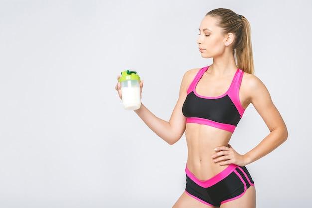 Mujer atractiva joven con batido de proteínas de dieta saludable bebiendo para el deporte y el fitness