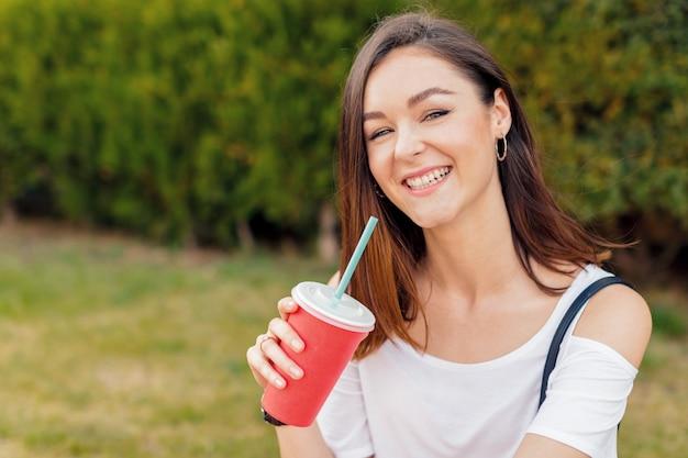 Mujer atractiva joven con una bebida en una calle en un día soleado