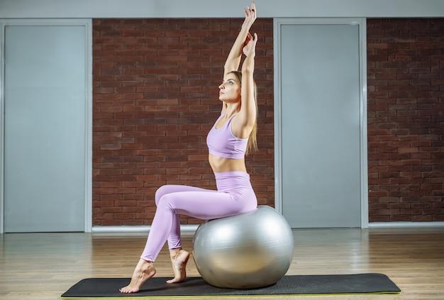 Mujer atractiva joven con la bola de la aptitud en el gimnasio