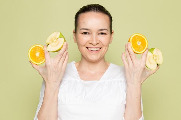 Mujer atractiva joven en camisa blanca con rodajas de manzanas y naranjas verdes
