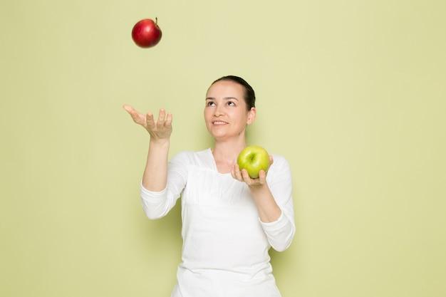 Mujer atractiva joven en camisa blanca sonriendo y jugando con manzanas verdes y rojas
