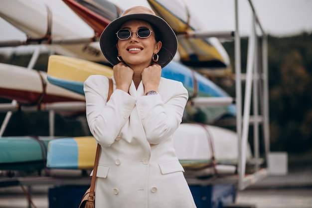 Mujer atractiva joven en chaqueta blanca caminando al aire libre