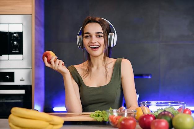 La mujer atractiva joven come la manzana roja y escucha la música en la cocina en la mañana. concepto de estilo de vida saludable, disfrutando del desayuno.