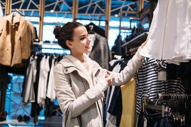 Mujer atractiva joven comprando ropa en el centro comercial
