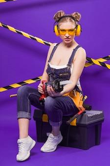 Mujer atractiva joven constructor en traje de mezclilla y gafas sentado en caja de herramientas negra