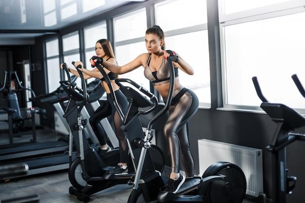 La mujer atractiva joven de los deportes se está resolviendo en gimnasio. haciendo cardio entrenando en cinta. corriendo en cinta