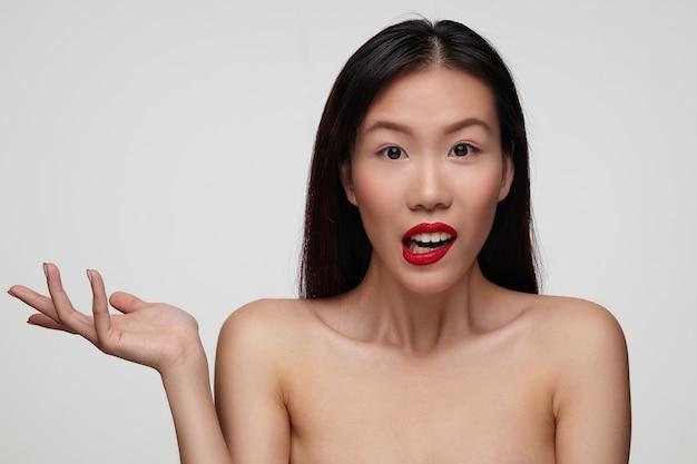 Mujer atractiva joven desconcertada con maquillaje festivo levantando confusamente la palma mientras mira con asombro, de pie sobre una pared blanca con los hombros desnudos