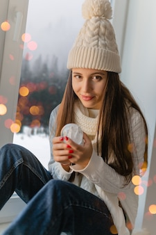 Mujer atractiva joven en elegante suéter de punto blanco, bufanda y sombrero sentado en casa en el alféizar de la ventana en navidad con decoración de presente de bola de nieve de cristal, vista del bosque de invierno, luces bokeh