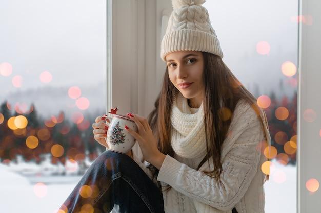Mujer atractiva joven en elegante suéter de punto blanco, bufanda y sombrero sentado en casa en el alféizar de la ventana en navidad sosteniendo una taza bebiendo té caliente, vista de fondo de bosque de invierno, luces bokeh