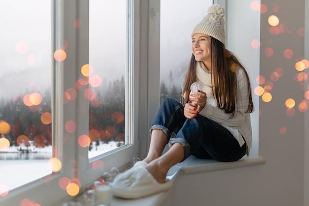 Mujer atractiva joven en elegante suéter de punto blanco, bufanda y sombrero sentado en casa mirando en la ventana sosteniendo la decoración actual de bola de nieve de cristal, vista del bosque de invierno, luces de navidad bokeh
