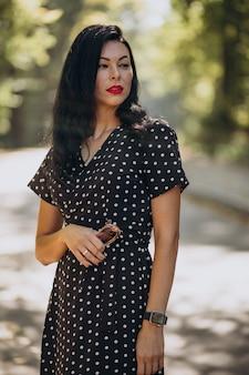 Mujer atractiva joven en elegante vestido de pie en el bosque