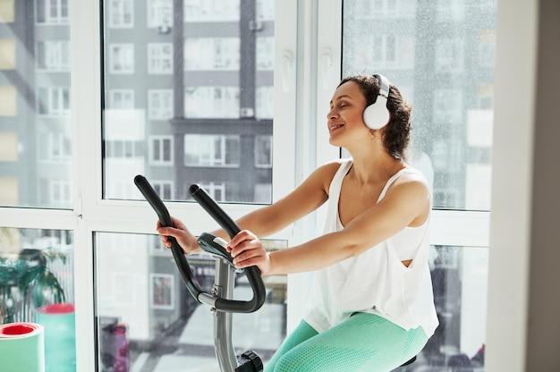 Mujer atractiva joven escucha la música mientras hace ejercicio en bicicleta de spinning