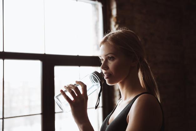 Mujer atractiva joven fitness agua potable.