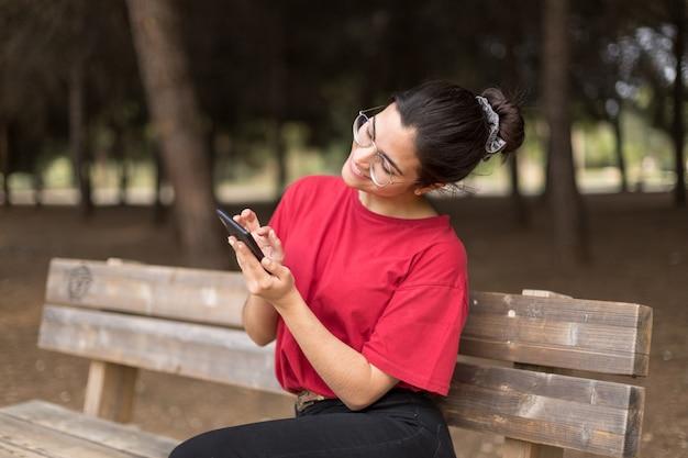 Mujer atractiva joven con gafas sentado en un banco y usando su teléfono en un parque, con una camisa roja. sevilla, españa