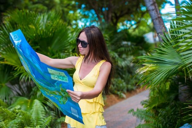 Mujer atractiva joven con gran mapa de la isla en la selva