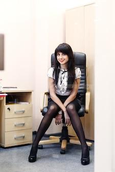 Mujer atractiva joven en las medias negras que se sientan en lugar de trabajo en oficina