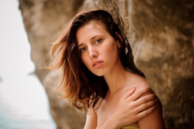 Mujer atractiva joven pelirroja en bikini amarillo de pie cerca de la roca