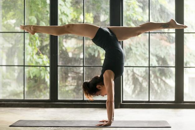 Mujer atractiva joven en la postura del handstand, fondo casero
