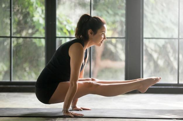 Mujer atractiva joven en la postura del handstand, fondo del estudio
