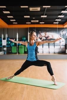 Mujer atractiva joven practicando yoga de pie en posición de virabhadrasana