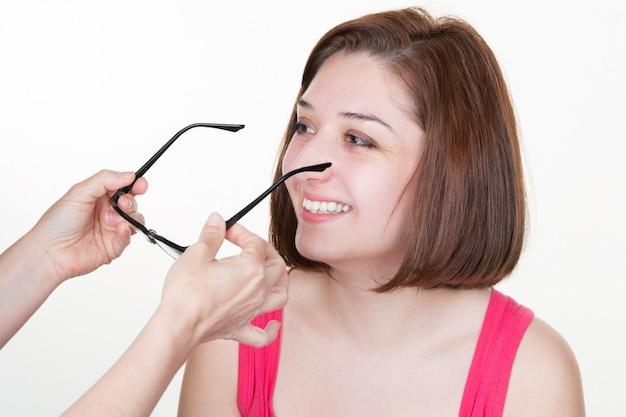 Mujer atractiva joven probando gafas nuevas con chica óptica