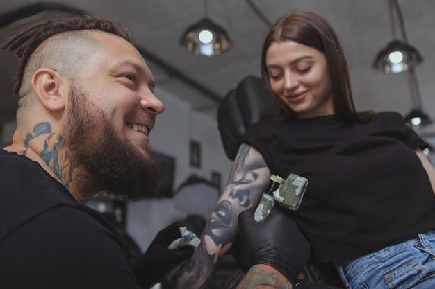 Mujer atractiva joven que consigue el nuevo tatuaje por el tatuador profesional