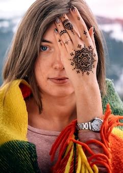 mujer atractiva joven que cubre el ojo con la mano mehndi