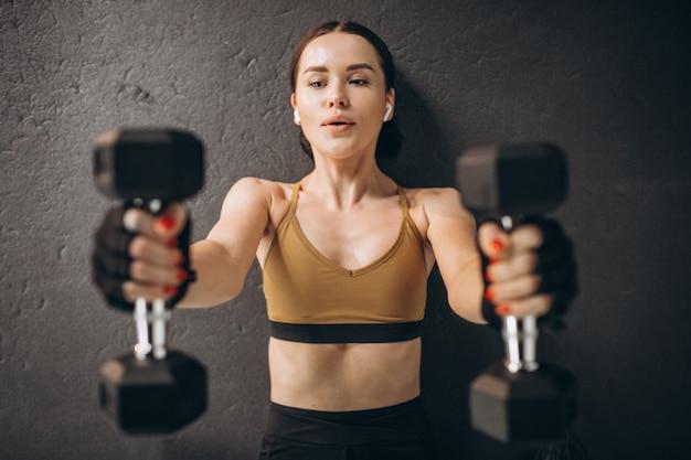 Mujer atractiva joven que ejercita con pesas en el gimnasio