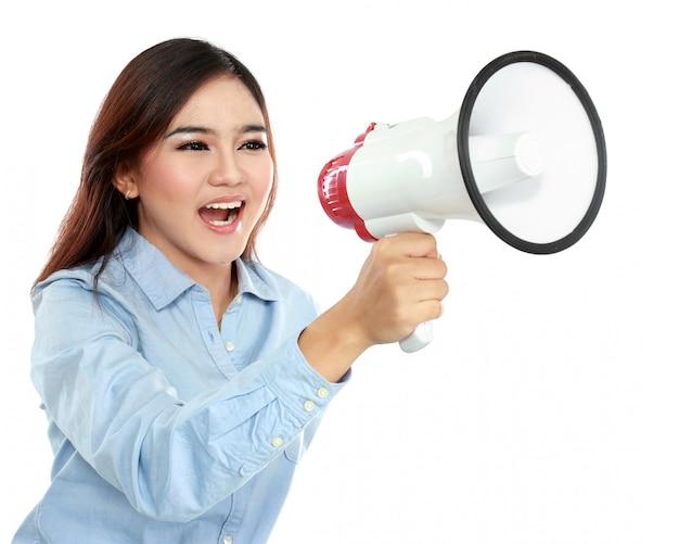 Mujer atractiva joven que grita usando el megáfono
