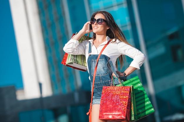 Mujer atractiva joven que habla en un teléfono celular y que lleva bolsos de compras