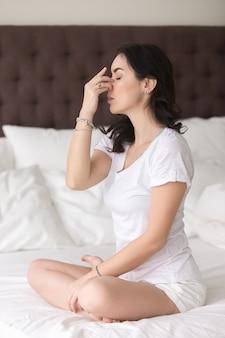 Mujer atractiva joven que hace actitud alterna de la respiración de la fosa nasal encendido