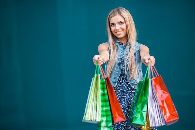 Mujer atractiva joven que hace compras y que habla en el móvil