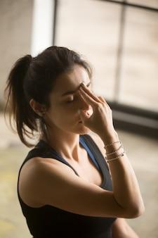 Mujer atractiva joven que hace la respiración alternativa de la fosa nasal