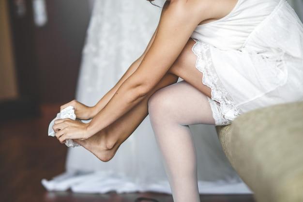 Mujer atractiva joven que lleva las medias blancas que ponen en sus piernas delgadas.