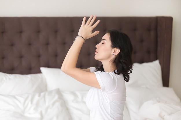 Mujer atractiva joven que medita en la cama, perfil