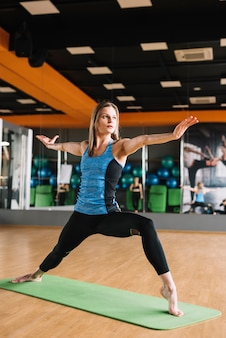 Mujer atractiva joven que practica yoga en la estera verde en gimnasio