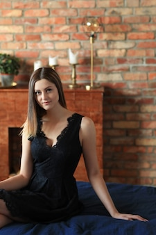 Mujer atractiva joven que presenta en el sofá