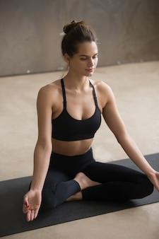 Mujer atractiva joven que se sienta en la postura fácil del asiento, estudio gris