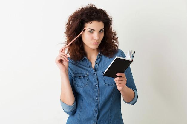 Mujer atractiva joven que sostiene el cuaderno y el lápiz, pensando, expresión seria de la cara, pelo rizado, pensativo, aislado, camisa azul del dril de algodón, aprendizaje del estudiante, educación