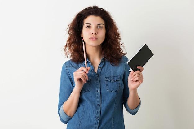 Mujer atractiva joven que sostiene el cuaderno y el lápiz, pensando