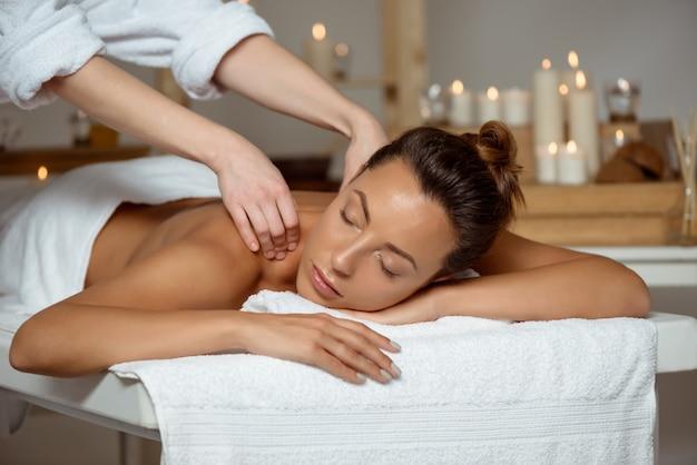 Mujer atractiva joven que tiene masaje que se relaja en salón del balneario.