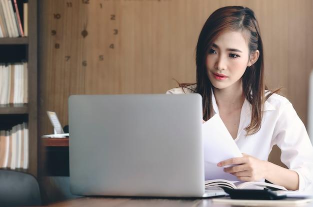 Mujer atractiva joven que trabaja con la computadora portátil mientras que se sienta en oficina de estilo vintage.