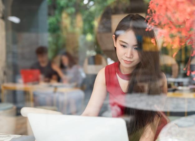 Mujer atractiva joven que usa la computadora portátil en cafetería - conexión social y concepto de estilo de vida